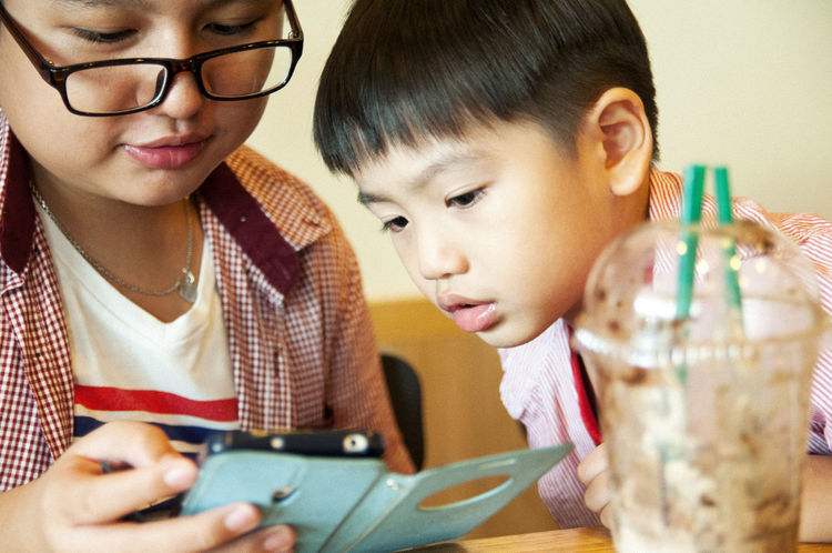 Closeup of kids looking at mobile device in cafe 11 Years Old 5 Years Old Asian  Boys Childhood Close-up Indoors  Kids Learning Lifestyles Looking Mobile Conversations Mobile Device Mobile Phone Natural Light People Smart Phone Technology Using