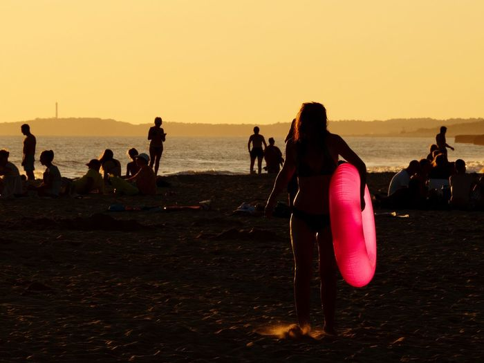Silhouette woman holding inflatable ring at beach against clear sky during sunset