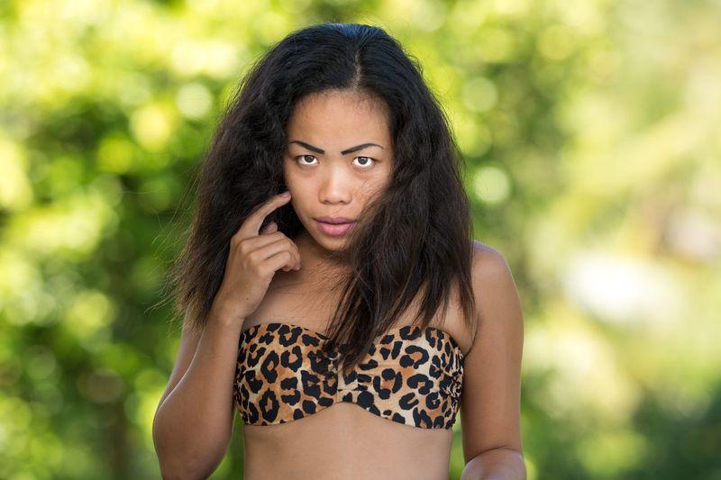 Woman in bikini top standing outdoors