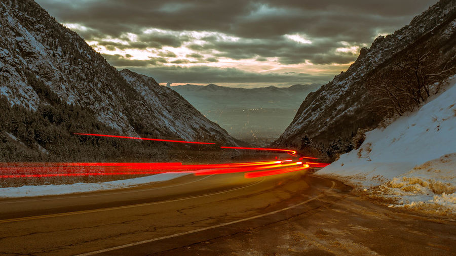 Light trails on road amidst mountains at dusk