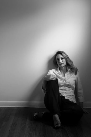 Full Length Portrait Of Woman Sitting On Hardwood Floor Against Wall