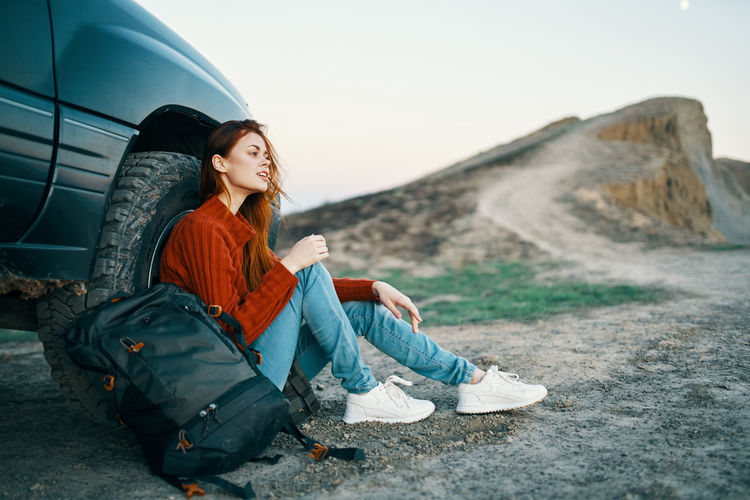 Young woman sitting on mountain against sky