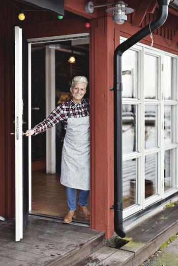 Full length of woman standing by door of building