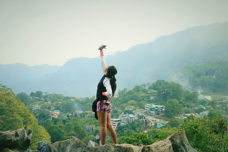 Woman taking selfie while standing on mountains