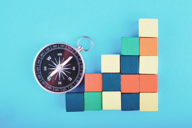 compass and colorful wooden cube on blue background Indoors  No People Geometric Shape Studio Shot Shape Still Life Close-up Blue Toy Direction Multi Colored Guidance Accuracy Circle Number Navigational Compass Colored Background Table Design Wall - Building Feature Blue Background