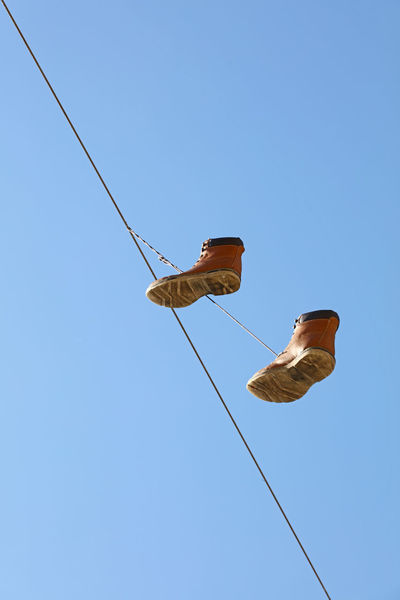 Suspended brown man shoes ower blue sky, low angle view Blue Cable Clear Sky Copy Space Dangle Day Foot Wear  Footwear High Low Angle View Military Military Style Overshoes Shoes Sky Streetart Streetphotography Suspended Swing Zippers Stories From The City #urbanana: The Urban Playground
