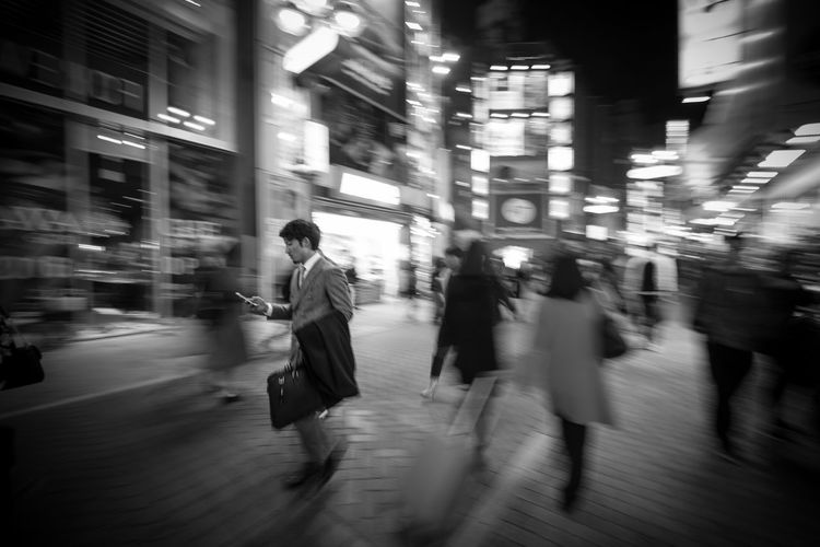 Mobile Conversations Motion Illuminated Walking City Night Speed City Life Long Exposure Architecture Real People People Group Of People Men Building Exterior Women Large Group Of People Rush Hour Adult Outdoors Tokyo man, walking down alley in Shibuya The City Light