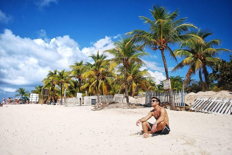 Mid adult man sitting on beach against palm trees