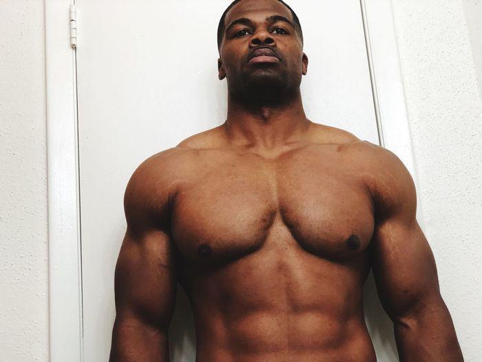 Shirtless Muscular Man Standing Against Door