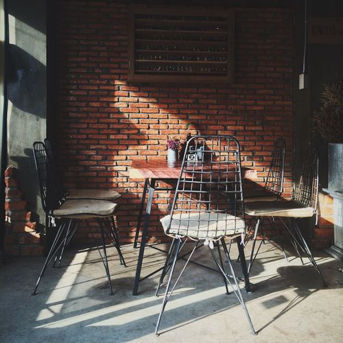 Empty Chairs And Table At Sidewalk Cafe Against Wall