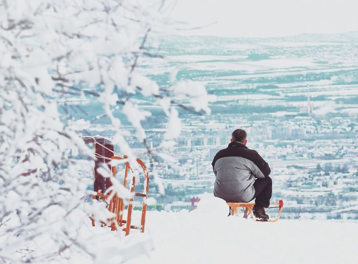 Rear view of man sitting on a slide against snow covered cityscape