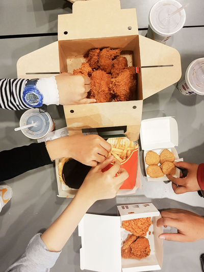 High angle view of woman holding food on table