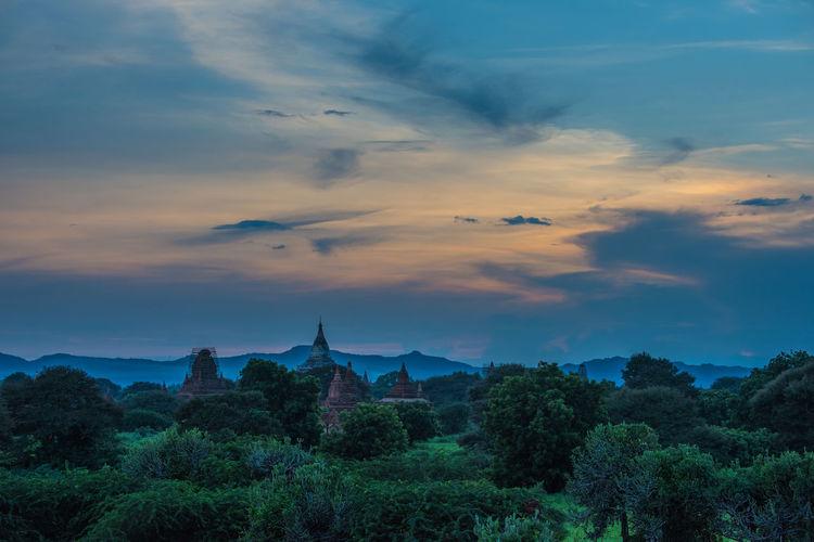 Pagoda amongst trees against dramatic sky