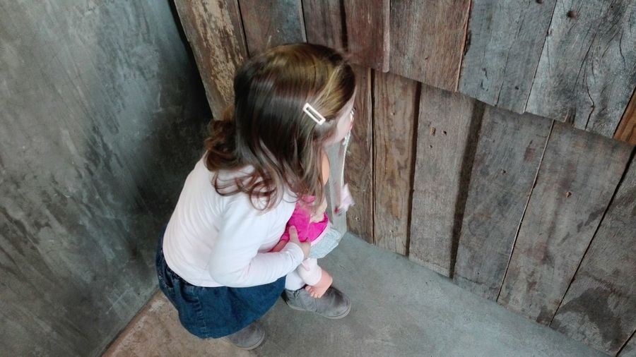 High Angle View Of Girl Peeking Through Wood Paneling While Hiding In Cabin