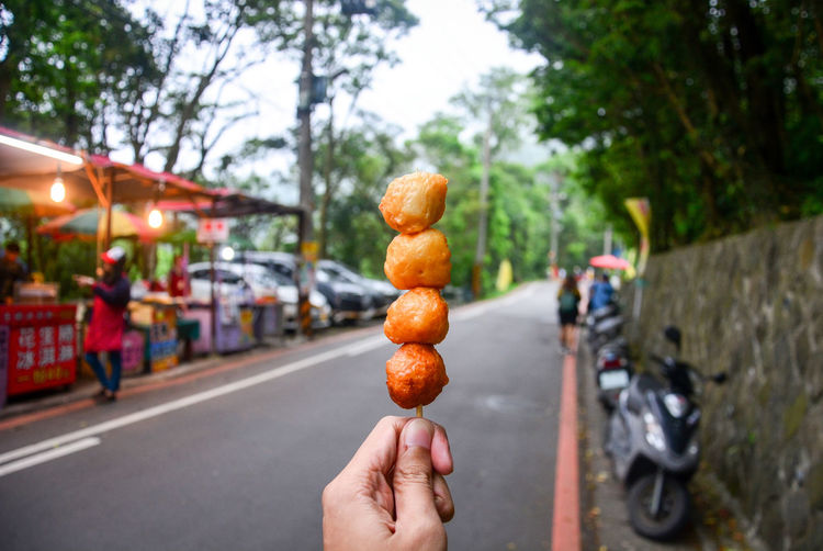 Street food, hand holding deep fried shrimp ball on the wooden skewer with food stall background