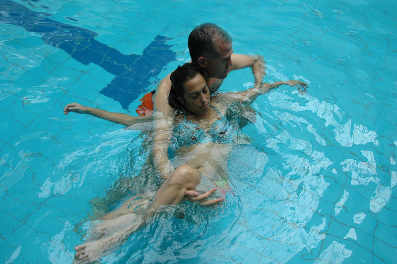 Man helping woman in swimming pool