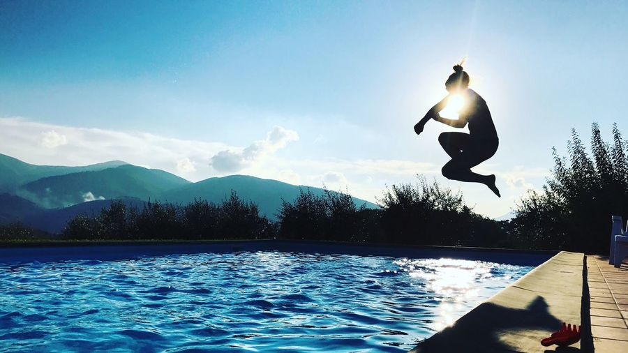 Silhouette woman jumping in swimming pool against sky