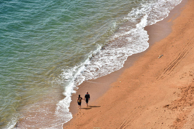 Shoreline Couple Two People West Bay Dorset Uk Beach Beauty In Nature Day High Angle View Land Motion Outdoors People Sand Sea Standing Water Wave Coastline Ocean Shore