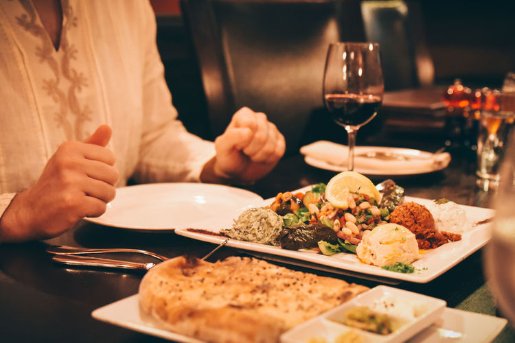 mid section of man sitting at a table ready to eat turkish food Appetizer Appetizers Beverage Dinner Drink Food Food Photography Liquor Meals Meze One Person Ready To Eat Turkish Food Wine Food And Drink Human Hand Mid Section Of Meal
