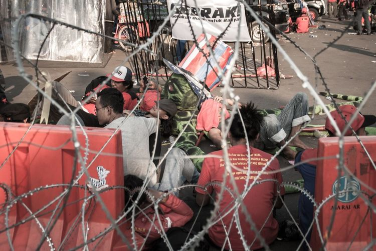 Protesters resting on road seen through fence in city