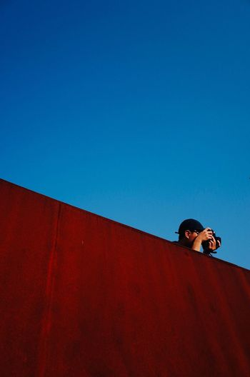 Low angle portrait of man against red wall against clear blue sky