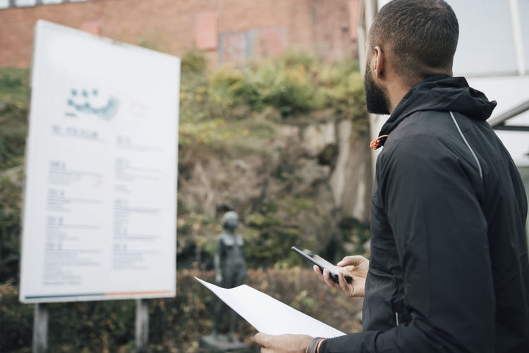 Side view of man with text standing on paper