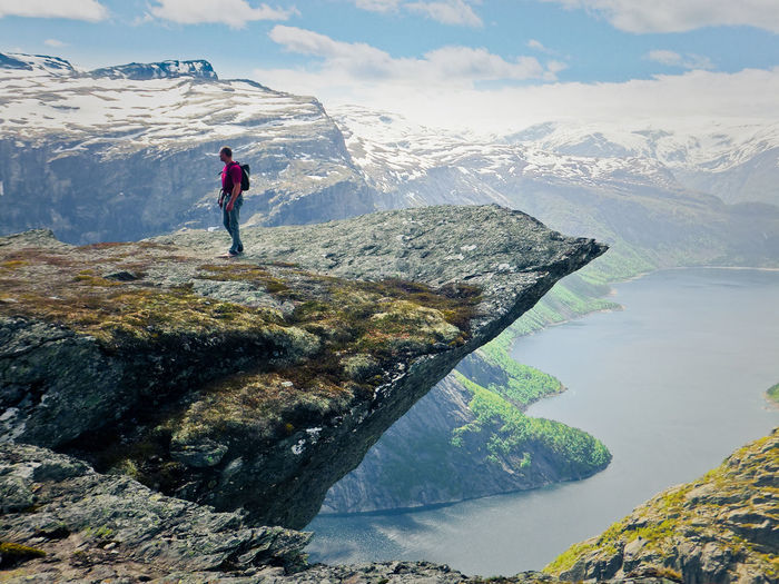 Man Standing Rocky Cliff Over Lake
