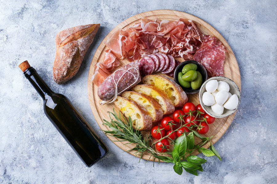 Set of meat antipasti served with herbs, mozzarella, tomatoes and olive oil on rustic wooden board over a stone background. Top view Antipasti Basil Food And Drink Ham Herb Olive Pork Snack Tapas Appetizer Board Cheese Feta Food Fresh Italian Meat Oil Parmesan Prosciutto Salami Sausage Stone Thyme Tomato