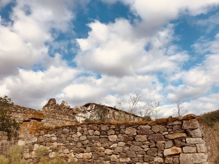 Low angle view of stone wall against sky