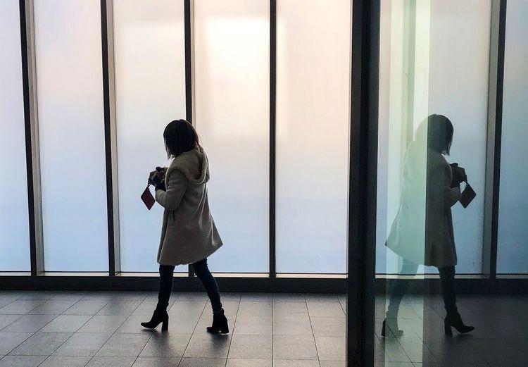 Full length of woman walking by window on floor