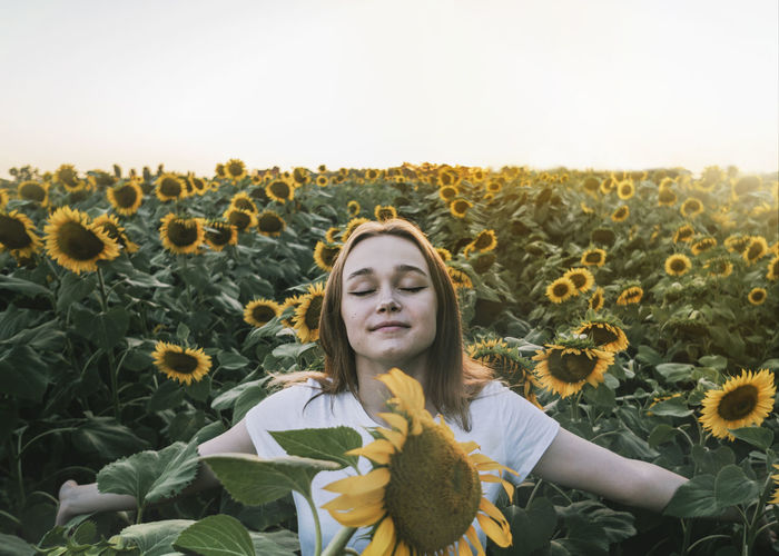 Portrait of young woman in sunflower field against sky