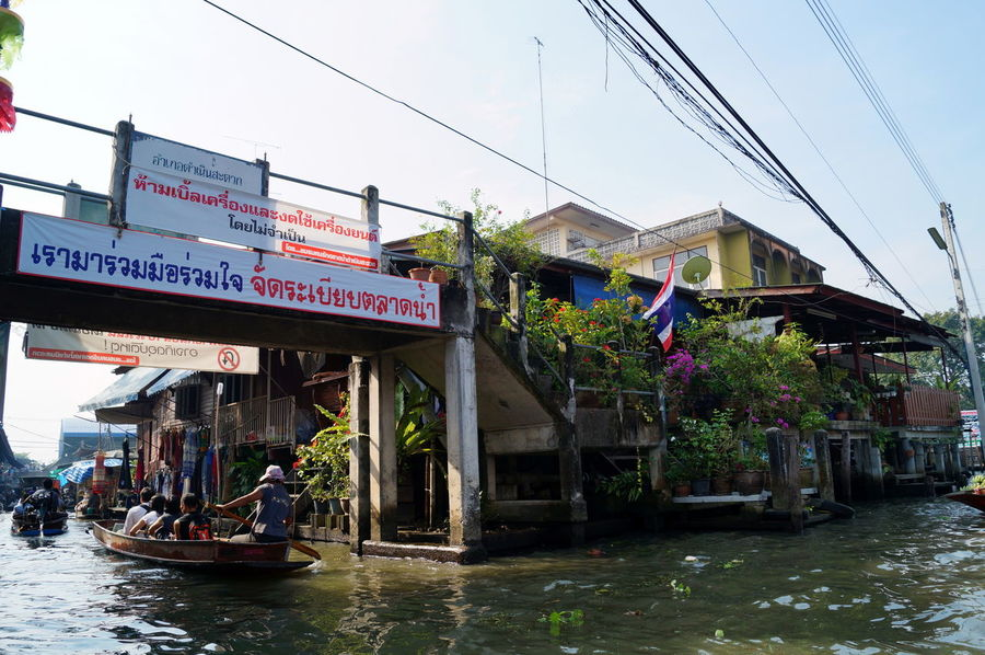 Architecture Bangkok Building Exterior Built Structure City Clear Sky Communication Day Floating Market House Incidental People Large Group Of People Non-western Script Outdoors Sky Spotted In Thailand Street Text Thai Thailand Transportation Tree Water Waterfront Western Script