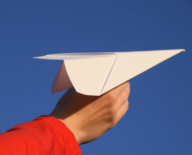 Low section of person holding paper against blue sky