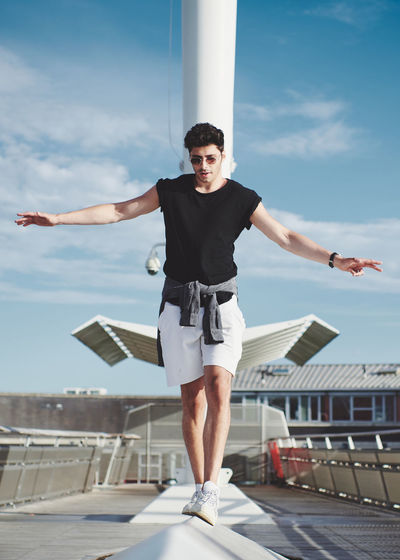Young man with arms outstretched standing against sky