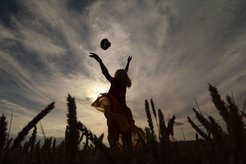 Low Angle View Of Woman Throwing Hat In Mid-Air On Field Against Sky