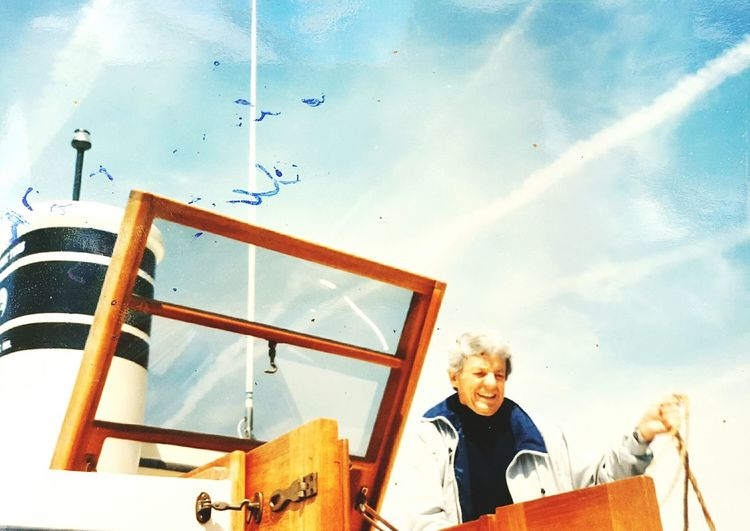 Happy man standing in ship against sky