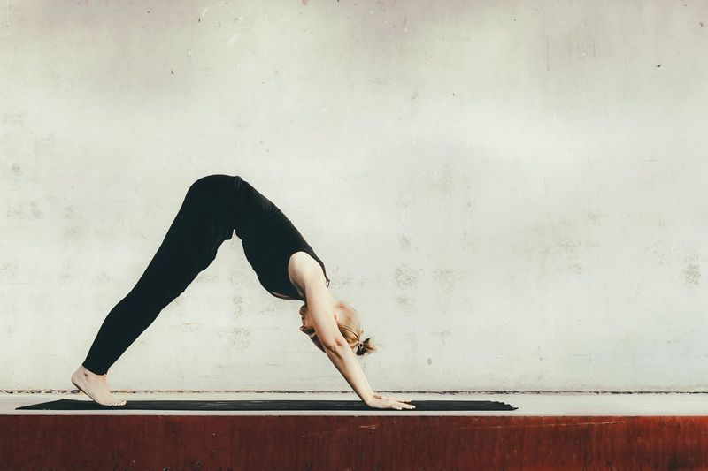 Full length of woman doing yoga against wall