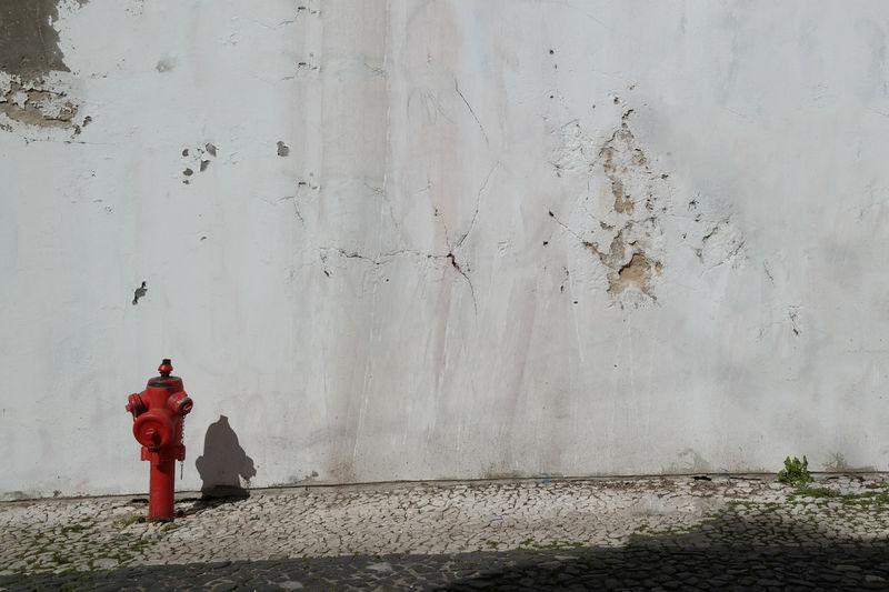 Red fire hydrant on sidewalk against grey concrete wall