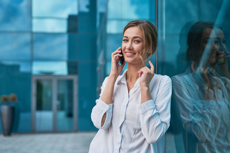 Portrait of smiling businesswoman standing by glass outdoors