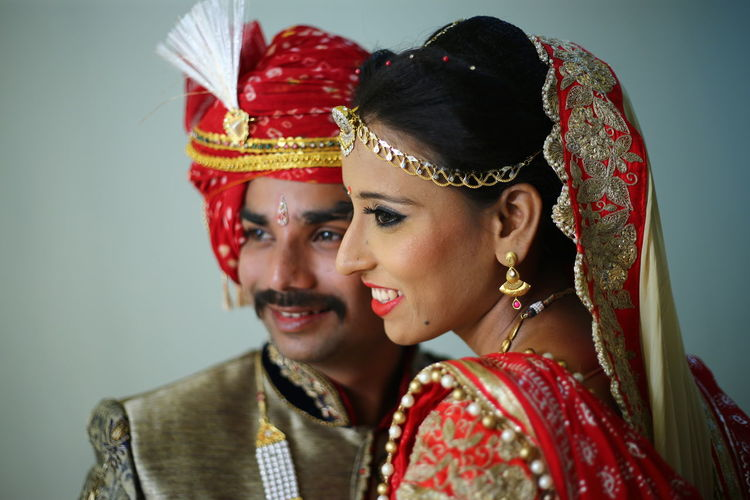 Close-up of smiling bride and groom standing in room
