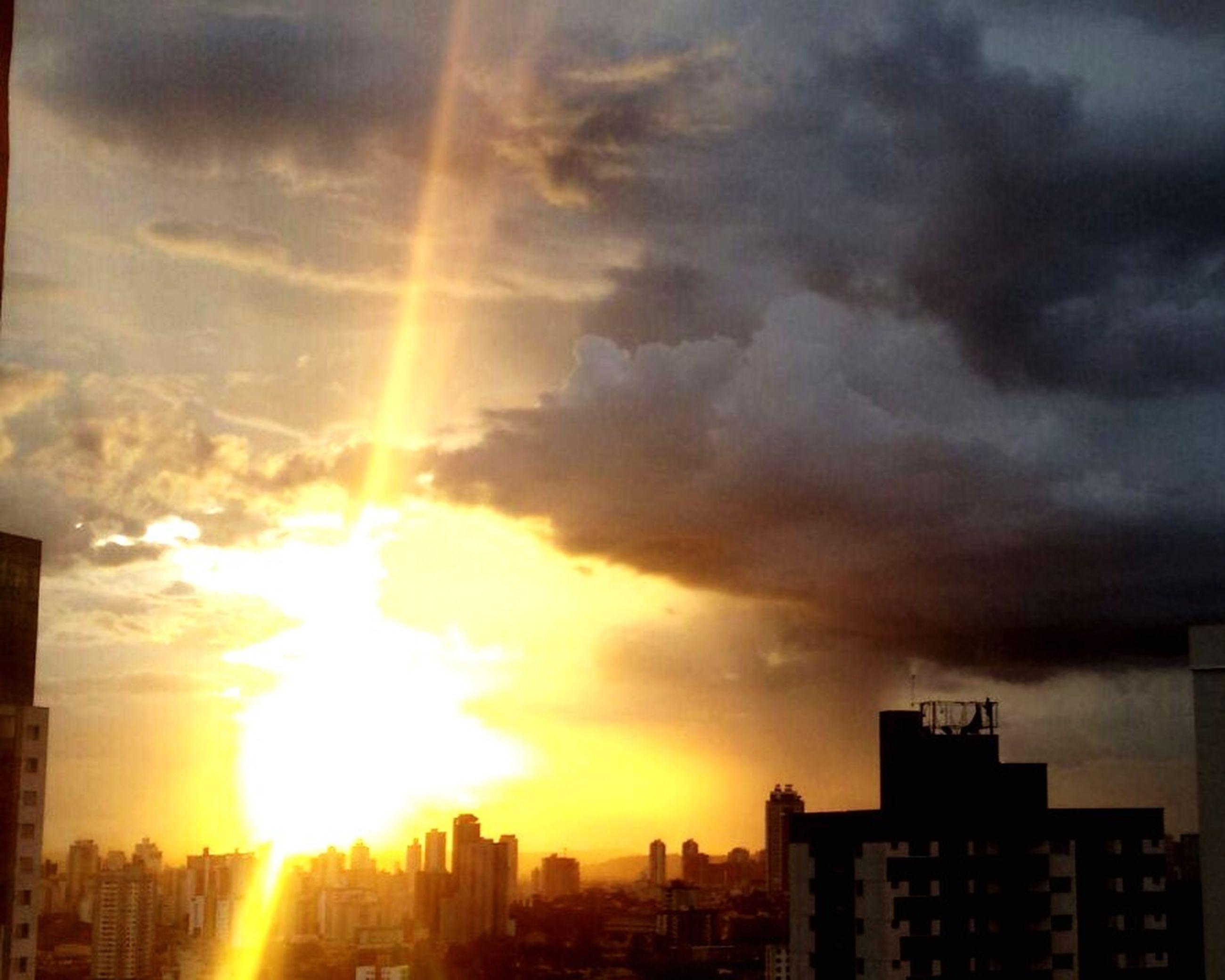 sunset, building exterior, architecture, built structure, sun, city, sky, cloud - sky, sunbeam, sunlight, cityscape, orange color, silhouette, residential building, building, residential structure, lens flare, cloudy, cloud, skyscraper