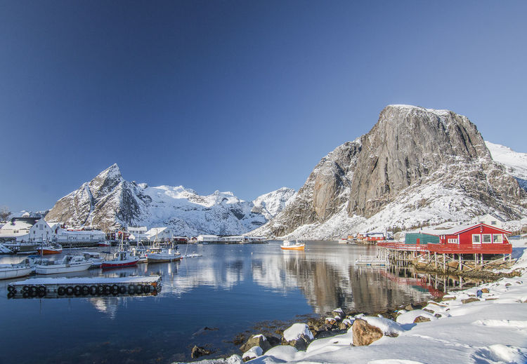 View on bay against snowcapped mountains Cold Temperature Winter Snow Mountain Water Beauty In Nature Scenics - Nature Sky Nature Day Mountain Range Clear Sky Tranquility Snowcapped Mountain Tranquil Scene Copy Space Frozen Ice No People Outdoors Norway Hamnøy