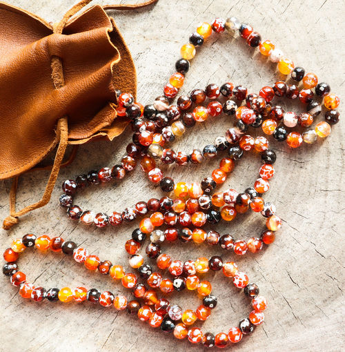 Sunny beads of amber fireplace faceted agate with leather jewelry pouch bag on rustic background Necklace Jewelry Bead High Angle View Still Life Decoration No People Indoors  Red Multi Colored Table Fashion Personal Accessory Large Group Of Objects Bracelet Holiday Celebration Leather Bag Pouch Rustic Style Faceted Crystal Ball Agate Stone Sunny Beads Stump