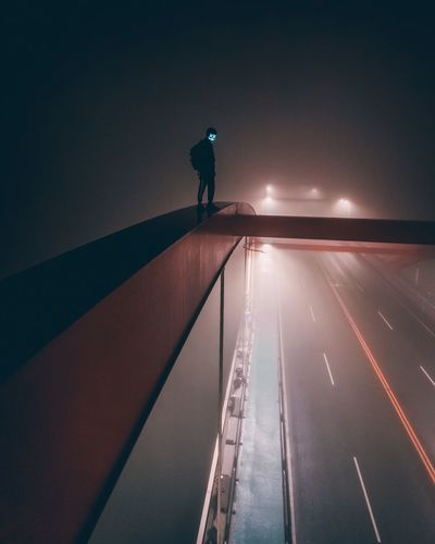 Silhouette man on illuminated road against sky at night