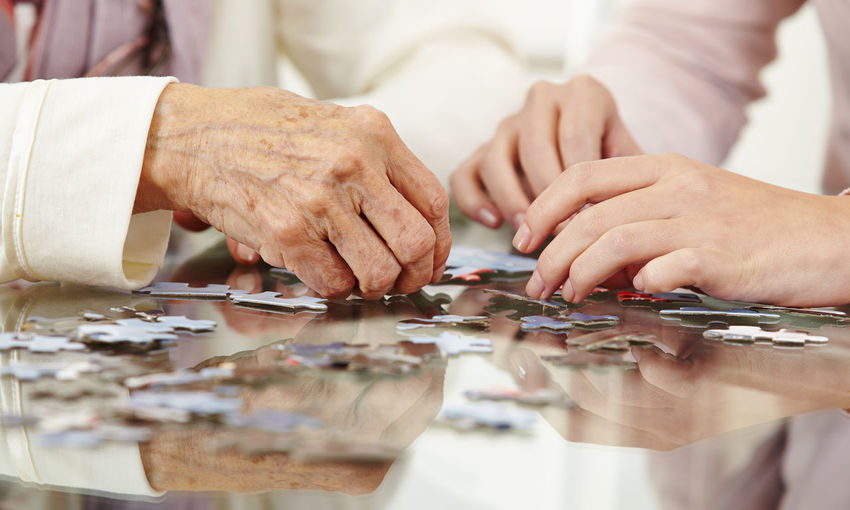 Midsection of grandmother and granddaughter solving puzzles on table at home