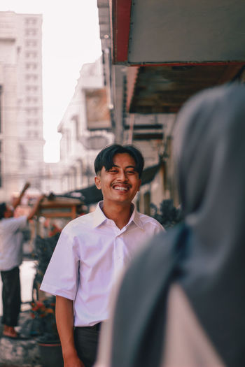 Portrait of smiling man standing on street in city