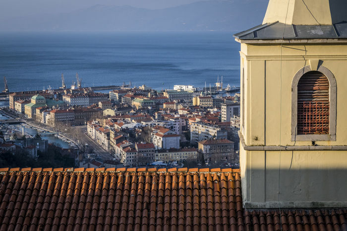 City of Rijeka view from Trsat, Kvarner bay of Croatia, old church detail in foreground. View from above on the city and harbor of Rijeka, Croatia. Church City Croatia From Above  Harbor Mobility In Mega Cities Rijeka View Architecture Building Exterior Built Structure Cityscape Day Foreground High Angle View Kvarner Bay Nature No People Old Outdoors Roof Sea Sky Trsat Water