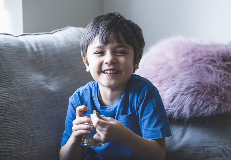 Portrait of happy boy holding medicine and water while sitting on sofa at home