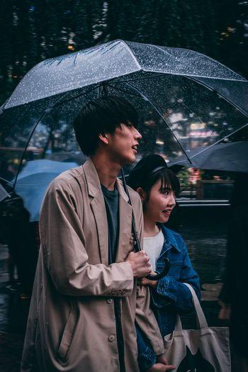 Man and woman standing at rain during rainy season