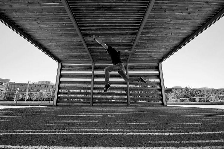 Man Jumping Below Bridge